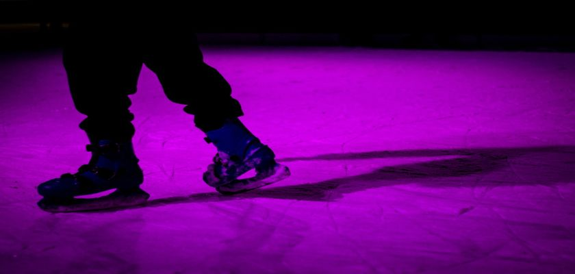 Ice skater skating on ice with a purple laser shining on the ice