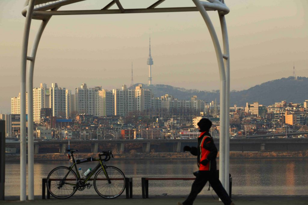 A man walking next to the bike path in Seoul. In the background you can see namsan tower