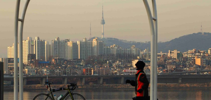 A bike sits before the Han River in Seoul. Namsan tower is in the background.