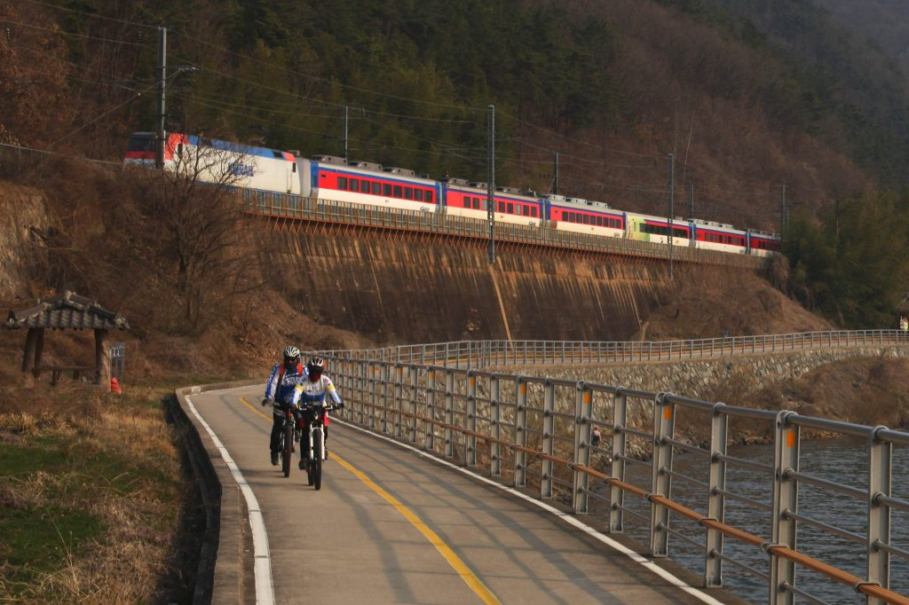 Cyclists ride on the designated bike path. A Korail train passes above.