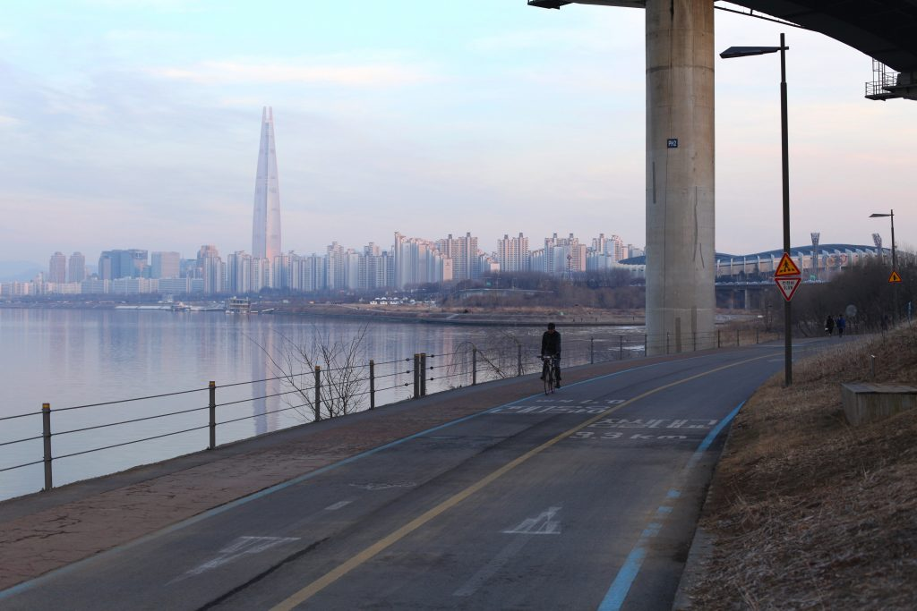 Lotte World Tower dwarfs twenty story apartment buildings. The Seoul Sports Complex peaks from behind a concrete bridge support.