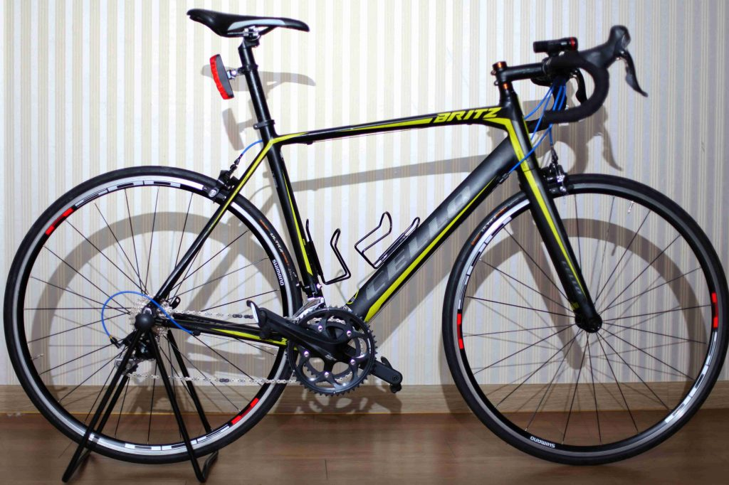 A photo of  road bike leaning against a wall