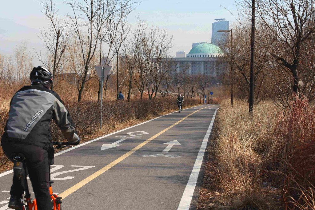 A biker rides the bike path onto Yeouido Island. The National assembly in Korea can be seen in the background.