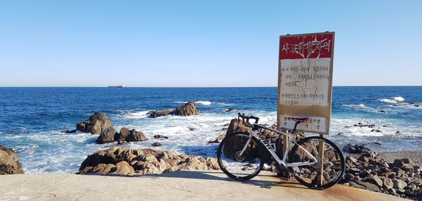 A bike resting next to a sign. The weather is clear and the sea is behind the bike
