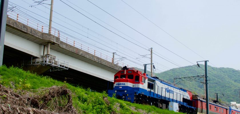 A Mugungwha train rolling down train tracks next to a country bike path in Korea.