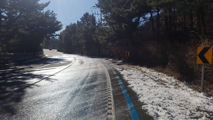 A icy Korean road in the winter, with snow covering the bike path. The climate during this season is cold and dry.