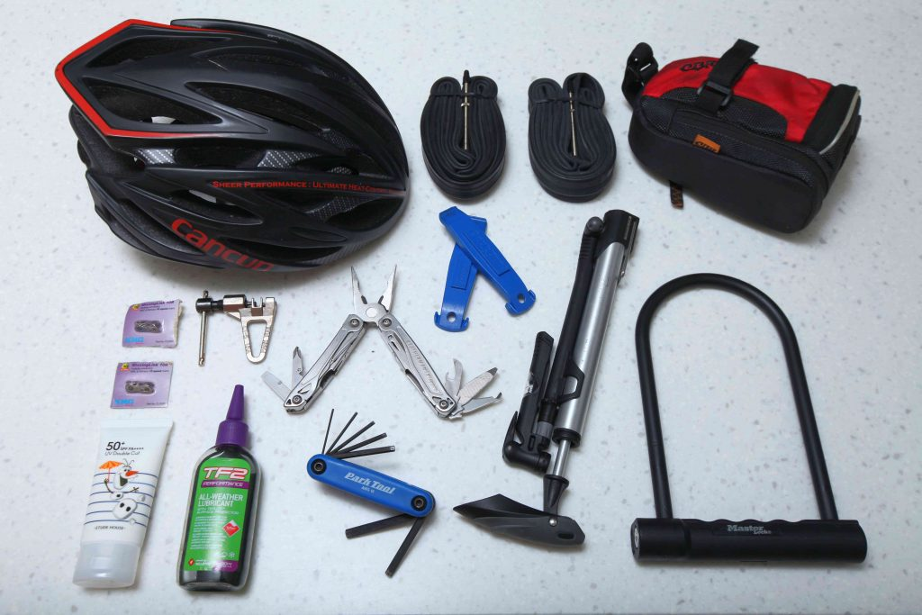 A basic bike tool kit. Left to right: helmet, tubes, saddle bag, quick links, chain breaker, multi-tool, tire levers, pump, u-lock, sunscreen, chain lube, hex wrench tool.