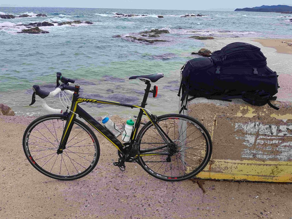 A road bike and a hiking backpack filled with tent and camping supplies.