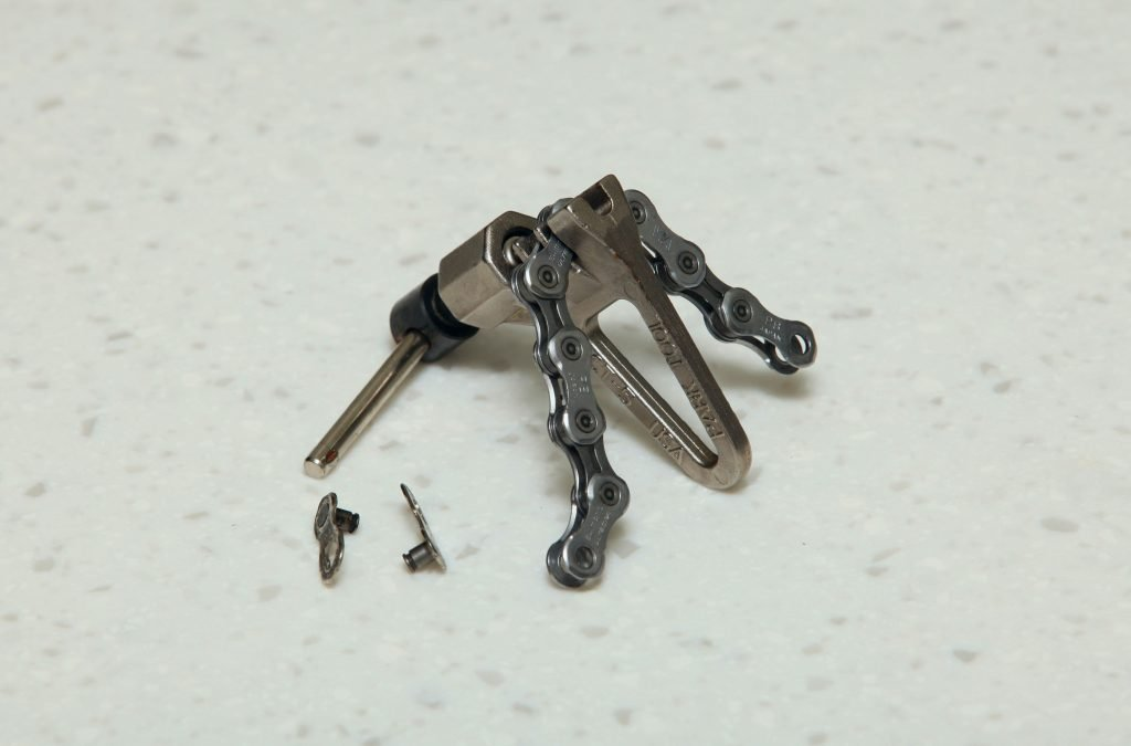 A picture of a chain breaker, chain, and quick links.