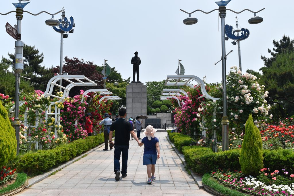 A photo in the summer of freedom park in Incheon. A man and a child are walking down the path towards the bronze stature of General McArthur. you can see the bronze state in the background.