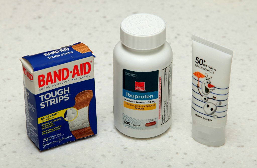 A picture of band-aids, ibuprofen, and sunscreen.