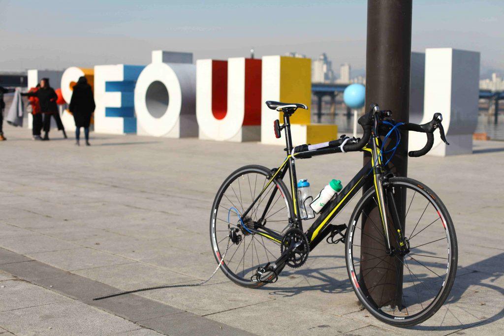A bike lays against a pole near the I·SEOUL·U sign in Seoul. It's bike chain lays on the ground.