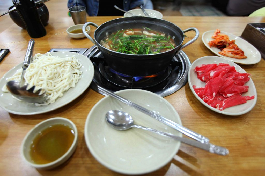 A meat and noodle (면; myeon) dish in a sit-on-the-floor restaurant. First, you cook the vegetables and meat. After, you add the noodles to the broth.
