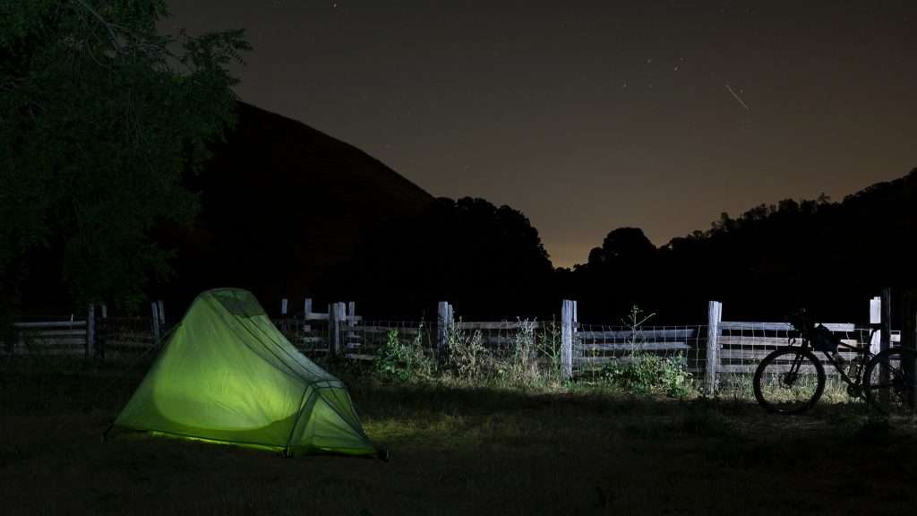 A tent and bike rest under the night sky.
