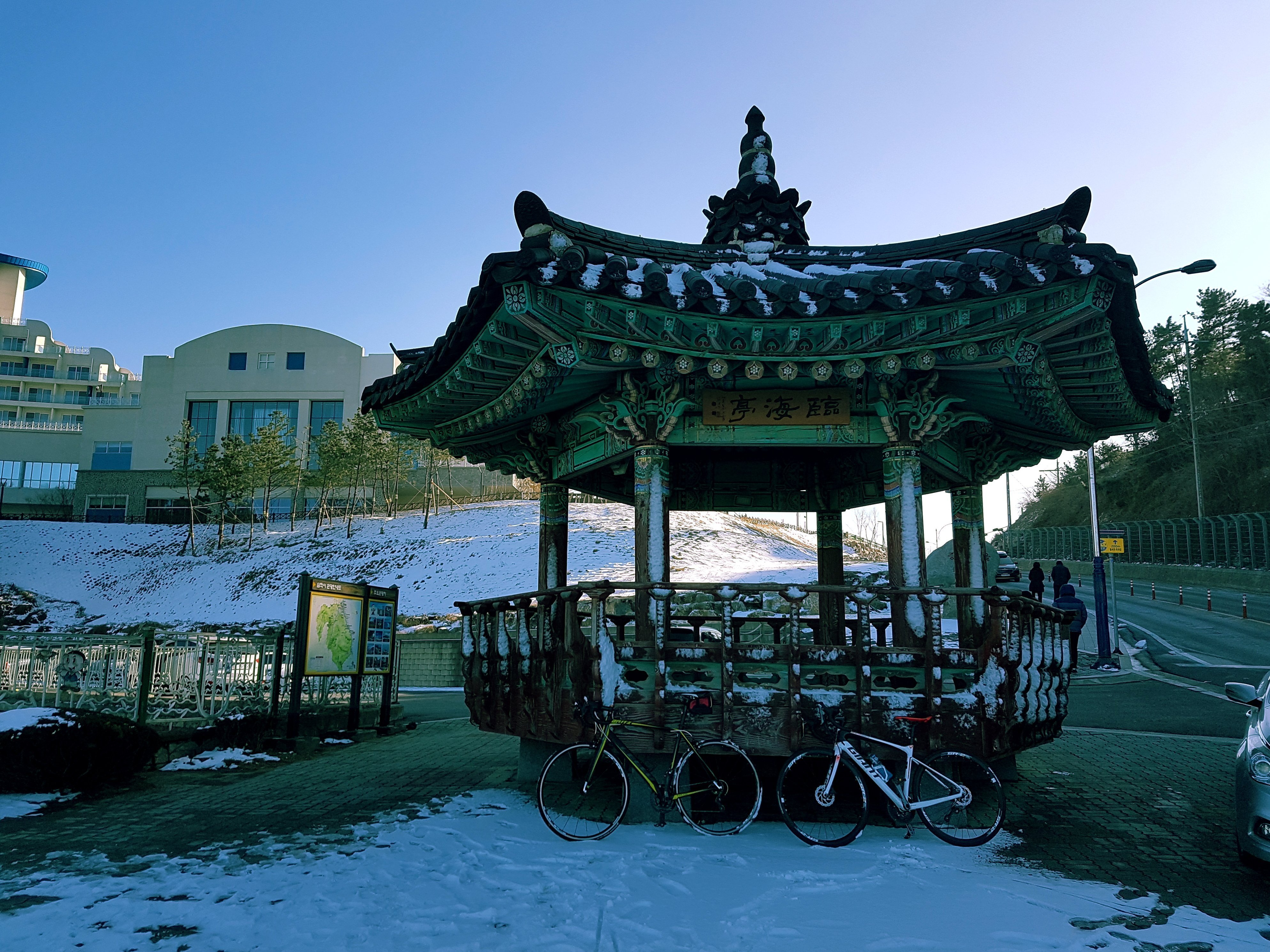 Two bikes sit against a gazebo covered in snow.