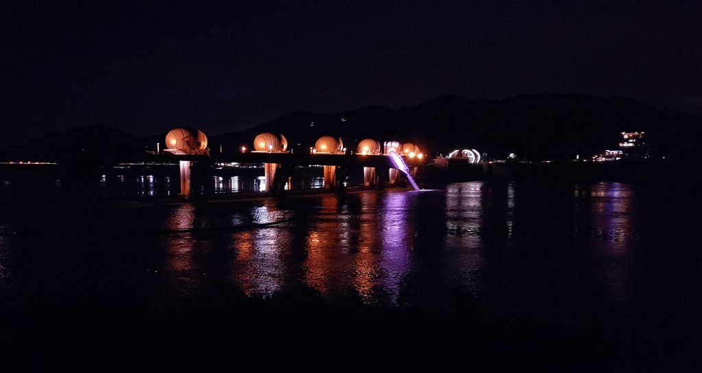 A photo of Ipobo Dam. Light from the egg-like orbs reflect off the waters of the South Han River.