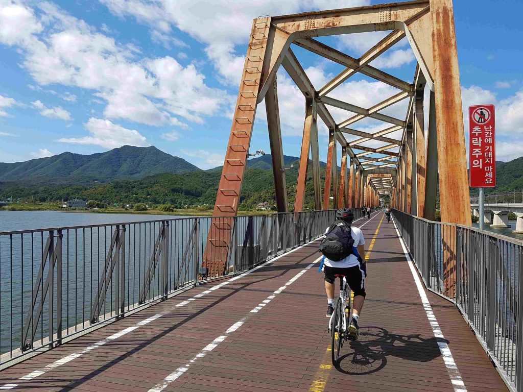 A cyclist cycling across a old railroad bridge outside of Seoul.