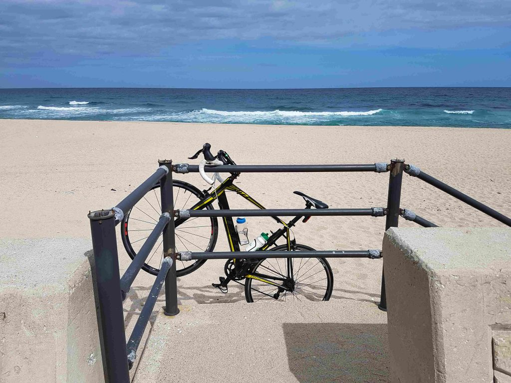 A bike rests on a fence. in the background there is a korean beach  with sand and waves