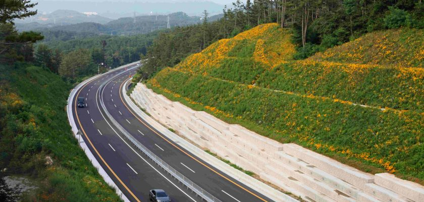 A highway in Korea. Orange flowers bloom on a hill above.