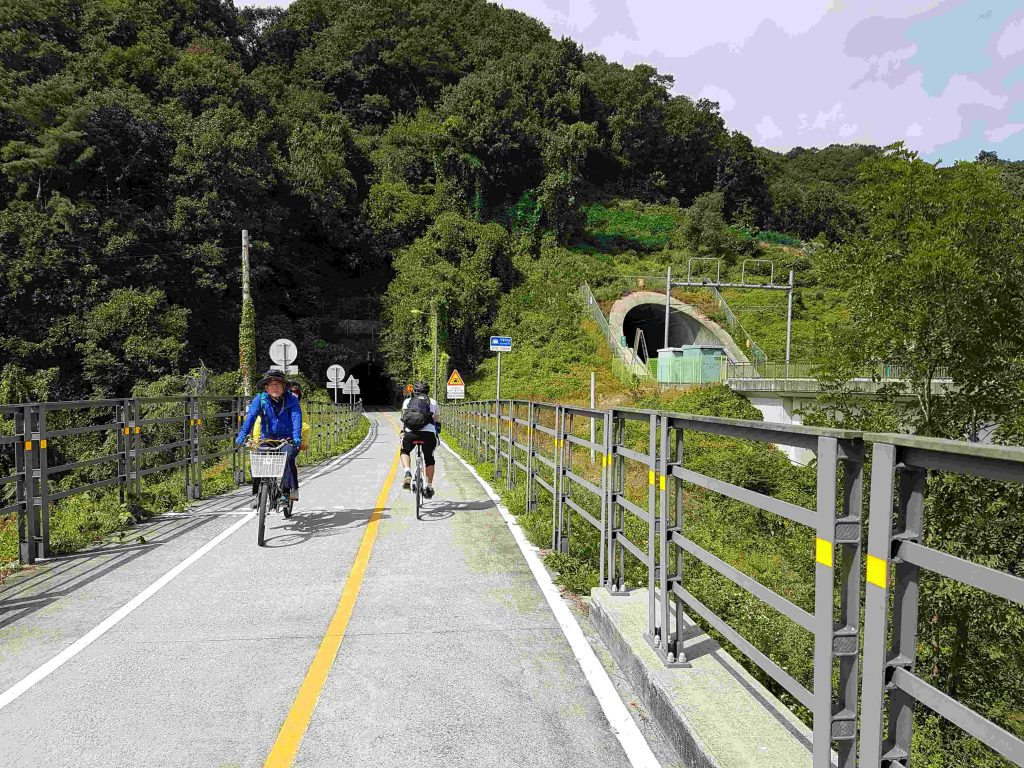 Cyclists ride along the bike path just outside of Hanam. A train tunnel and a bike tunnel dig into the hillside.