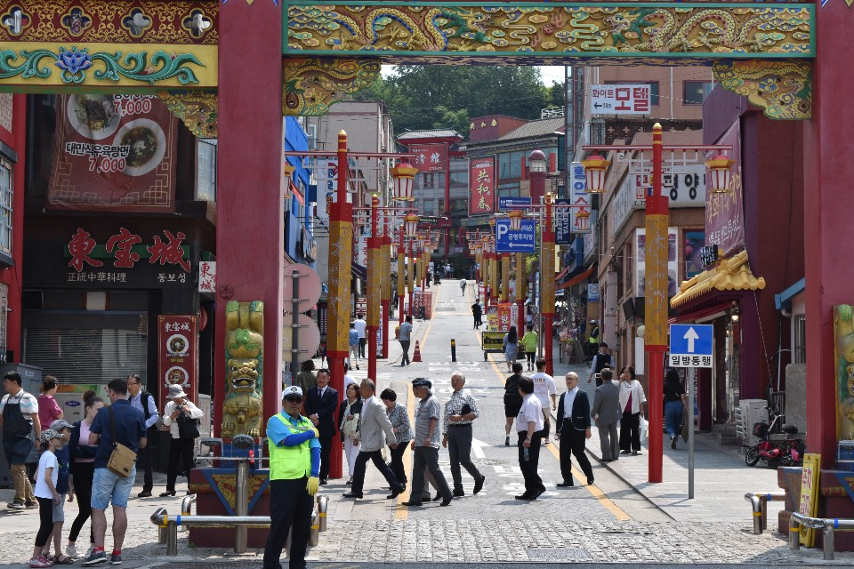 A photo of China street in Incheon chinatown. in the background people are walking up the street.