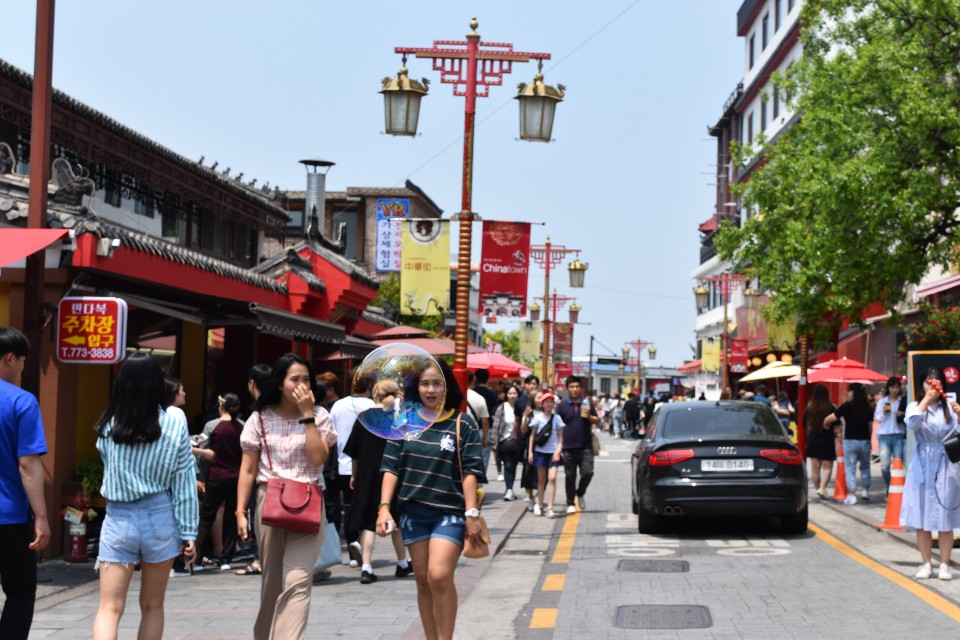 Two people walking down the main street in Incheon chinatown. In the background are people and chinatown restaurants
