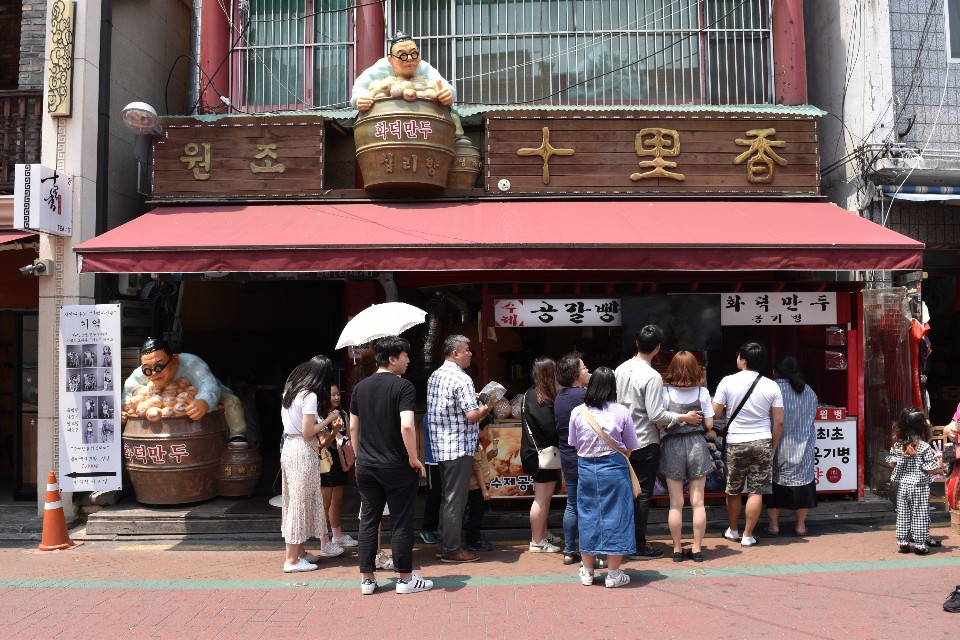 A photo if Simnihyang restaurant in Incheon Chinatown. There is a statue of a chinese man holding a pot of dumplings above the store entrance.
