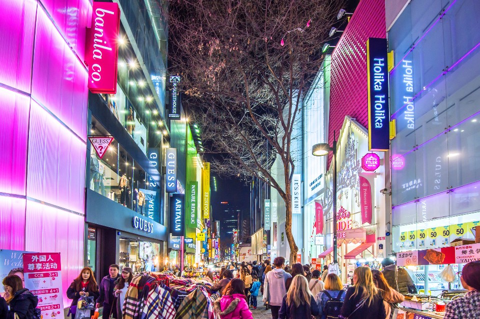 A photo of myeongdong at night. The photo shows a crowded street.