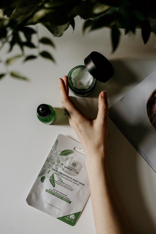 a photo of a  persons hand picking up a tub of green face cream