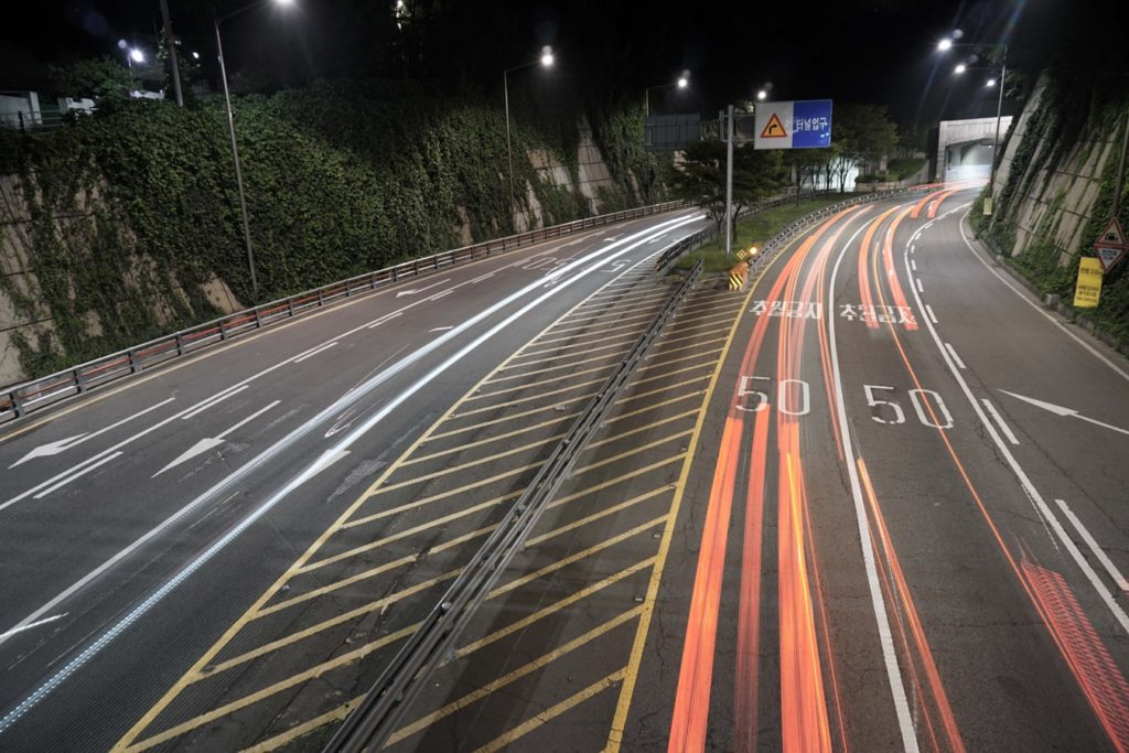 A  picture showing a Korean highway road with cars driving down