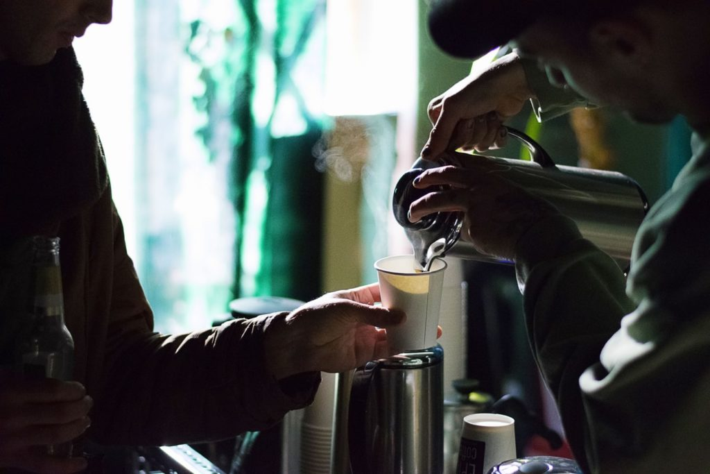 A man pouring hot water into a coffee cup