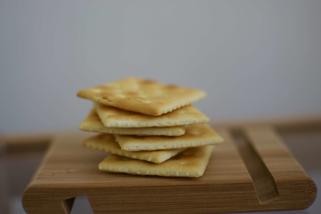 A photo of saltine crackers stacked up on a wooden plate