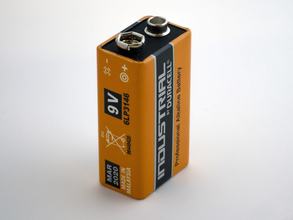 A photo of an orange 9V battery.