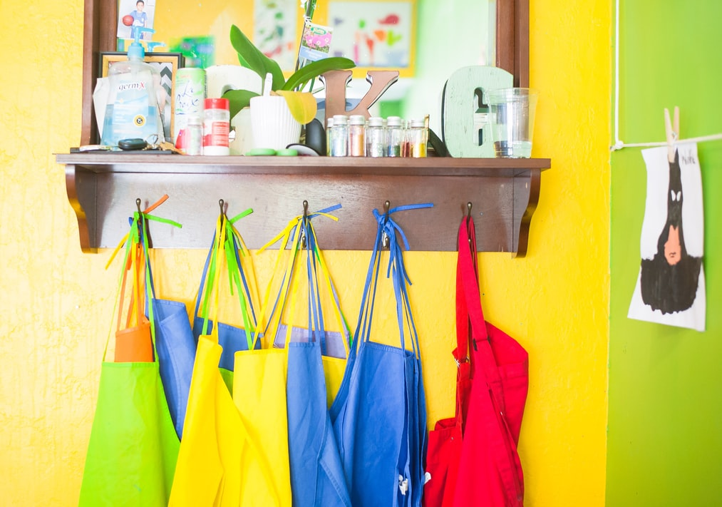 a photo of multi colored  aprons in a classroom
