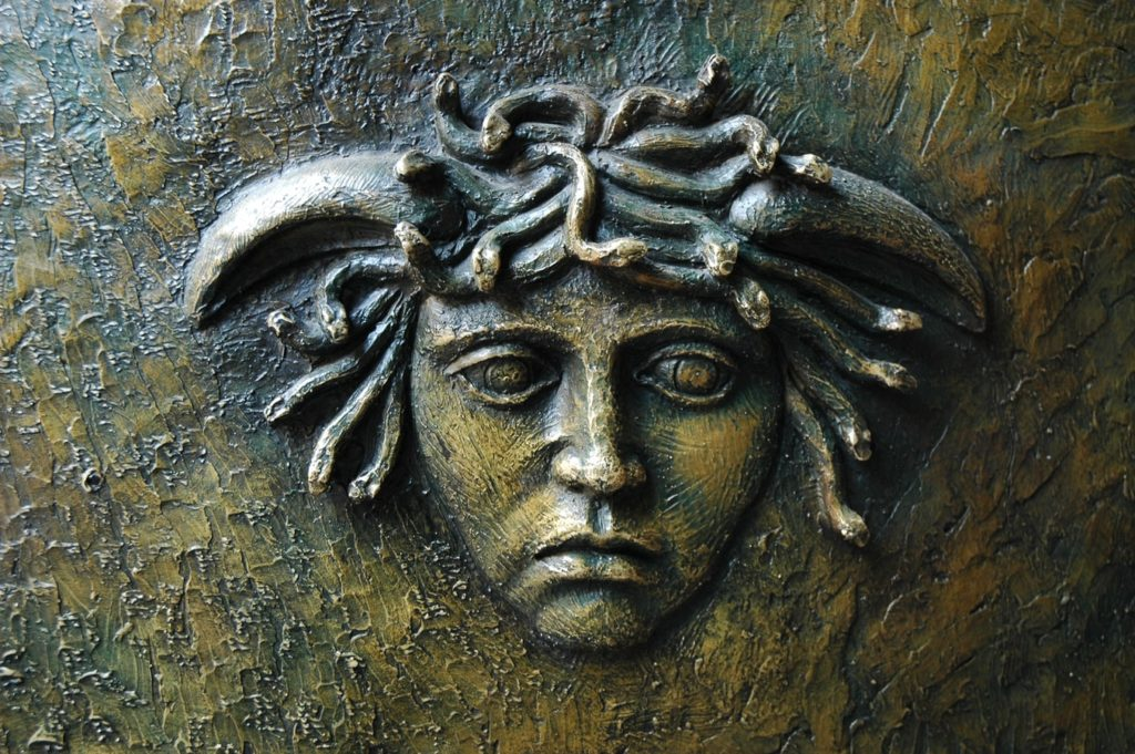 A stone statue of medusa that shows snakes in her hair.
